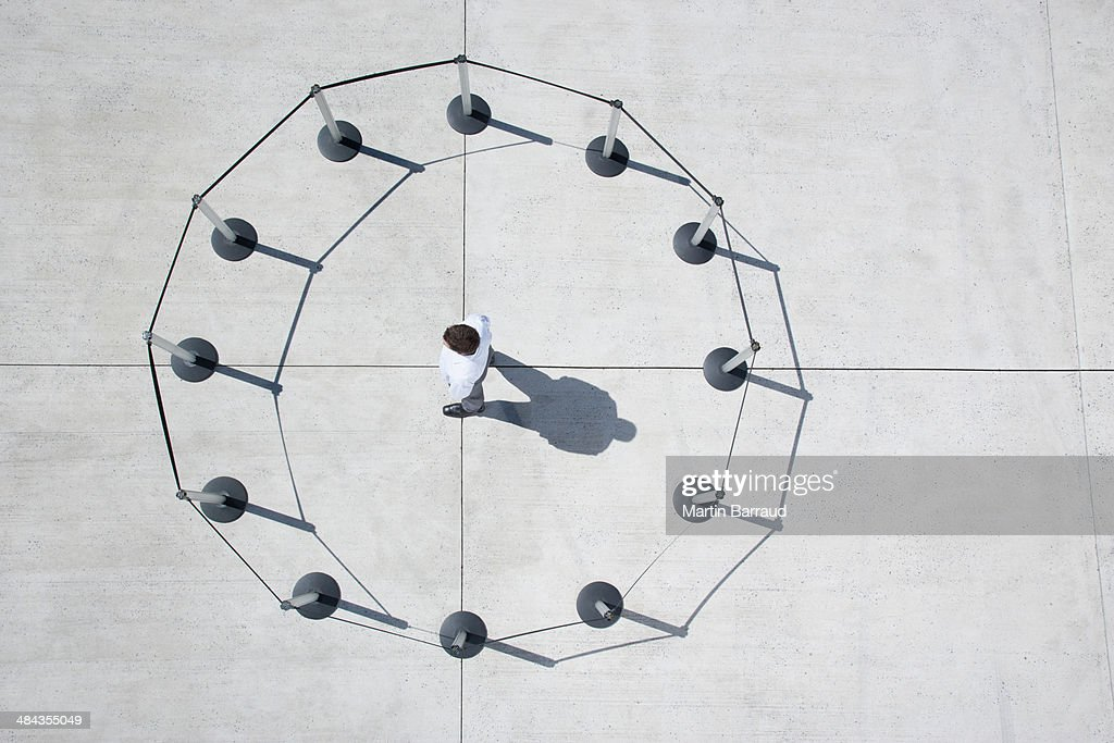 Man inside circle of cordon posts : Stock Photo
