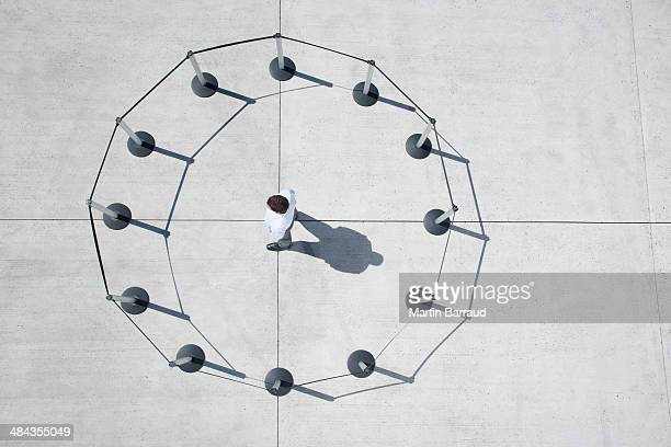 man inside circle of cordon posts - cordon boundary stock pictures, royalty-free photos & images
