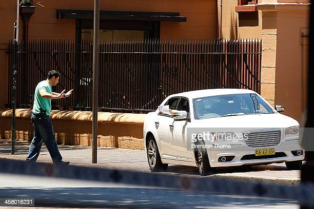 A man inside his vehicle hands a police negotiator a piece of paper outside NSW Parliament House on Maquarie Street on December 20 2013 in Sydney...