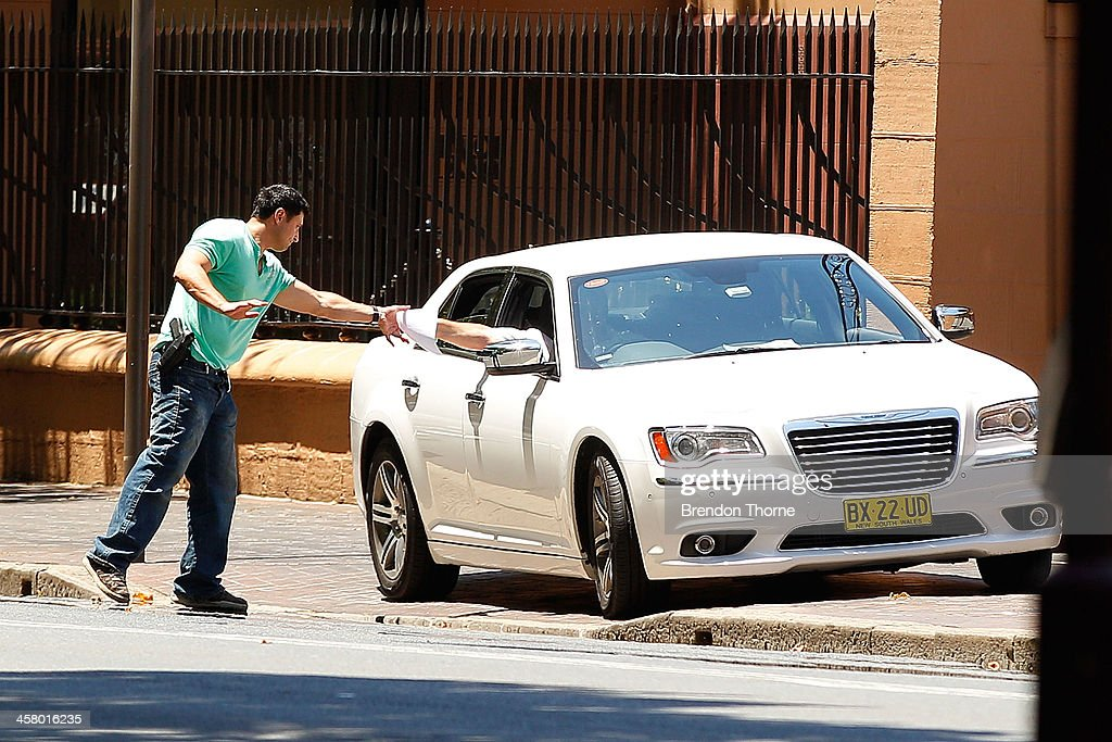 A man inside his vehicle hands a police negotiator a piece of paper outside NSW Parliament House on Maquarie Street on December 20, 2013 in Sydney, Australia. The NSW Parliament House was locked down due to a security threat outside the building. A man has been apprehended after a stand off with riot police.