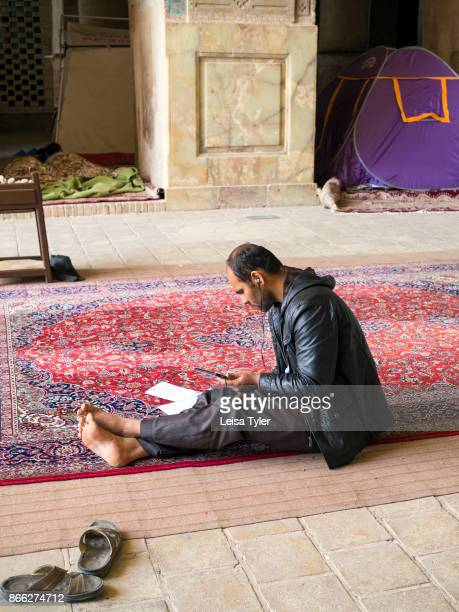 A man inside the Masjede Jame in Esfahan the oldest Friday mosque in Iran The mosque is a good example of the evolution of Iranian Islamic mosque...