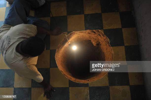 A man inspectas a sinkhole formed in a house on July 19 2011 in the north of Guatemala City When neighbors heard the loud boom overnight they thought...