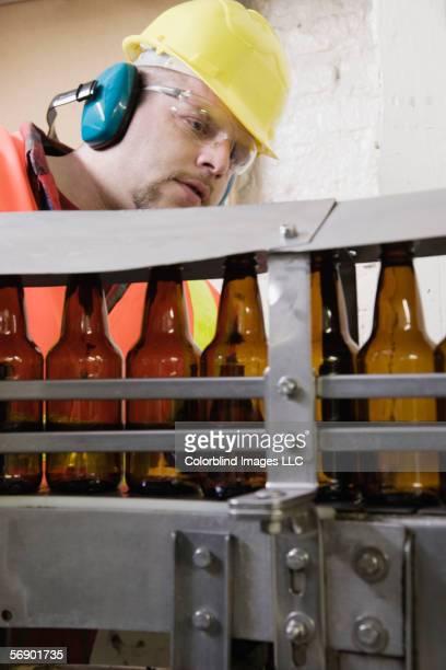 Man inspecting bottles on conveyor belt