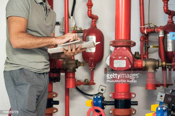 man inspecting fire protection sprinkler system - verification stock pictures, royalty-free photos & images