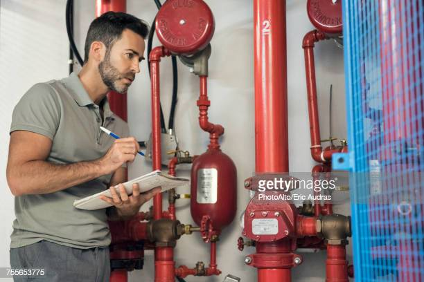 Man inspecting fire protection sprinkler system