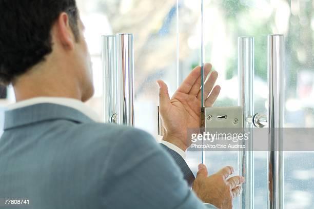 Man inspecting lock on glass door