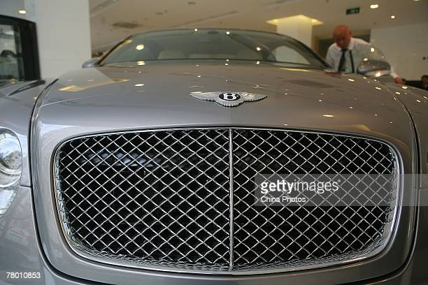 A man inspects a Bentley sedan in a Bentley flagship store on November 19 2007 in Shanghai China The United Kingdom based company has posted record...