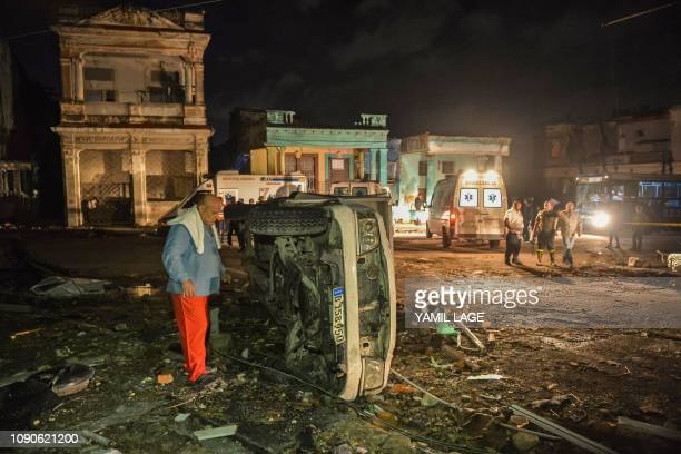 A man inspects a damaged car lying on its side in the tornadohit Luyano neighborhood in Havana early on January 28 2019 A rare and powerful tornado...