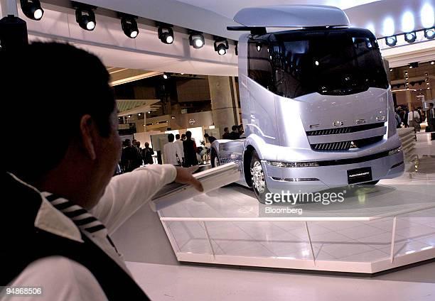 A man inspects a Mitsubishi Fuso concept truck on display at the 38th Tokyo Motor Show on Tuesday November 2 at Makuhari east of Tokyo Mitsubishi...