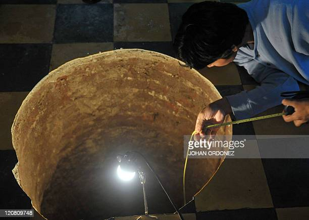 A man inspects a sinkhole inside a house on July 19 2011 north of Guatemala City When neighbors heard the loud boom overnight they thought a cooking...