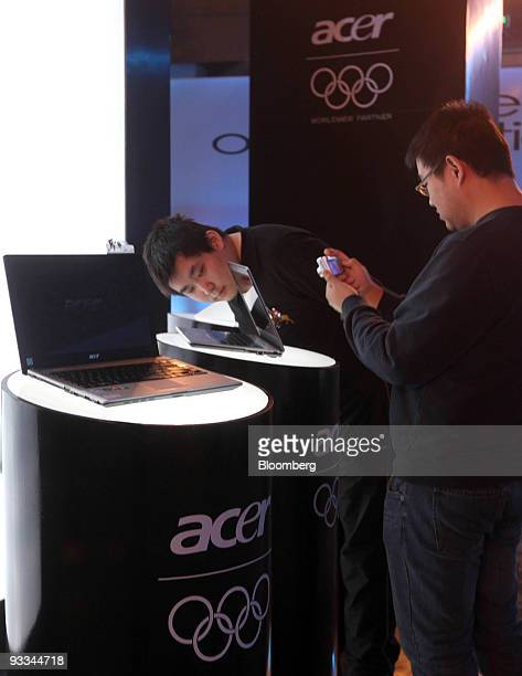 A man inspects an Acer Inc laptop computer while another takes a photograph at a media event in Beijing China on Tuesday Nov 24 2009 Acer Inc is the...