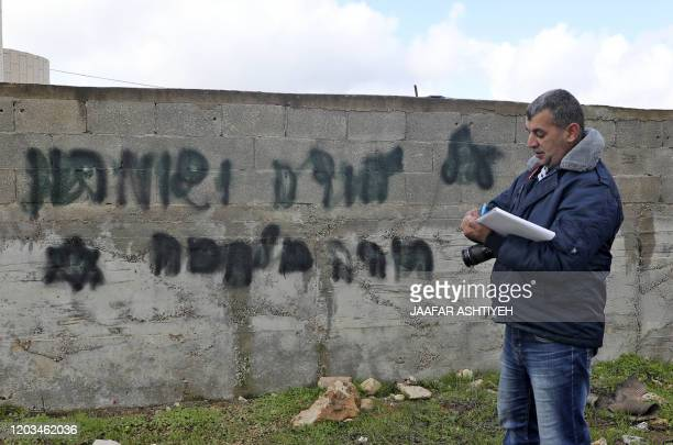 A man inspects an antiArab slogan daubed on the wall in the occupied West Bank village of Yasuf near Nablus on February 26 2020 Israeli police said...