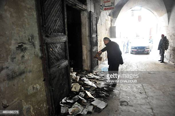 A man inspects burnt books on January 4 2014 in north Lebanon's majority Sunni city of Tripoli a day after a decadesold library owned by a Greek...