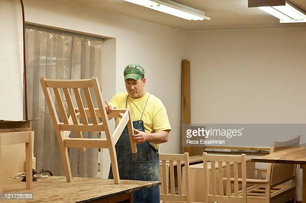 Man inspects half made chairs