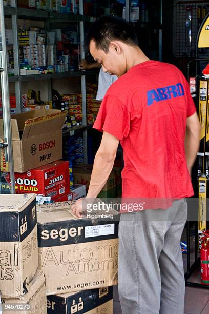 A man inspects recently received goods at an automotive spare parts market in Guangzhou China on Saturday July 7 2007 Exports of engine parts wheels...