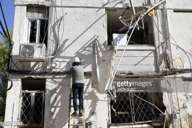 A man inspects the damage of a building caused by a rocket strike on the southern Israeli city of Ashkelon near the Gaza border on May 5 2019 Gaza...