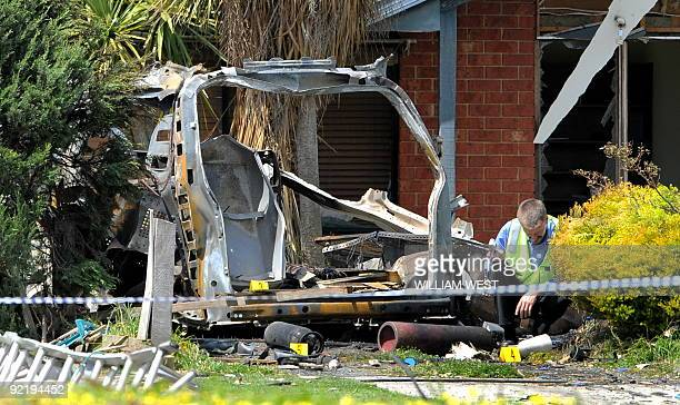 A man inspects the remains of a plumber's van after it was torn apart by an explosion as an apprentice went to unlock it using a keyless entry device...