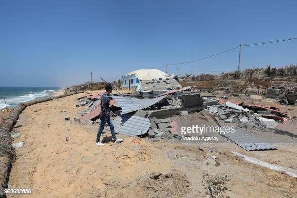A man inspects the wreckage of houses and tents that belong to Palestinian resistance group after the warplanes of Israel carried out an airstrike...