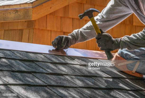 man installing asphalt roof - roof stock photos and pictures