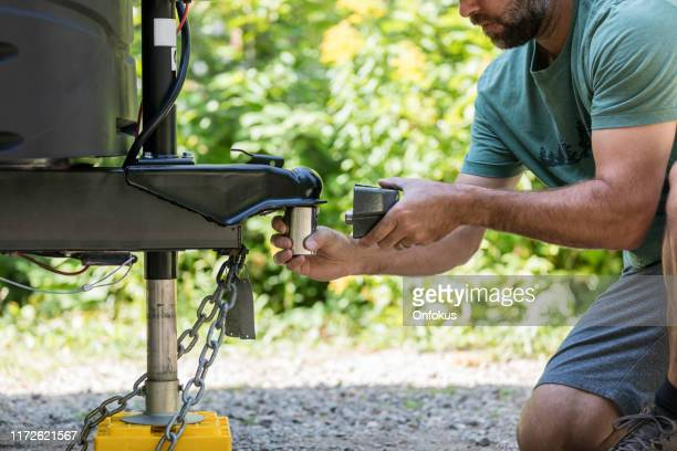 man installing camper trailer padlock during camping in summer - trailer stock pictures, royalty-free photos & images