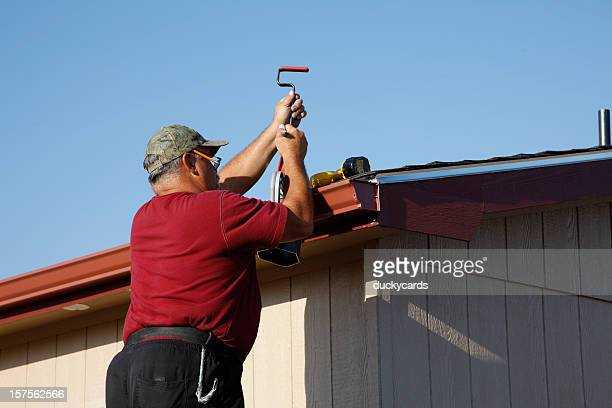 Man Installing Downspout and Seamless Gutters