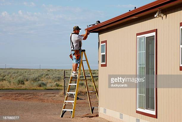 man installing downspout and seamless gutters - roof gutter stock photos and pictures