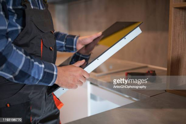 man installing induction hob in new kitchen - burner stove top stock pictures, royalty-free photos & images