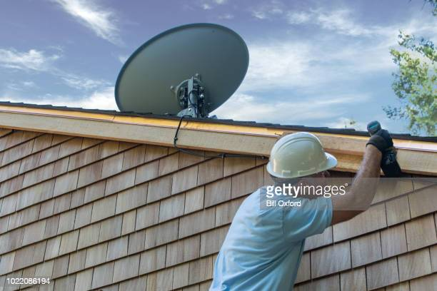 man installing satellite dish - receiver stock pictures, royalty-free photos & images