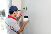 Man installing security alarm system