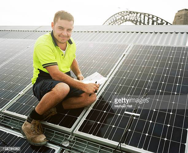 Man installing solar panels on roof