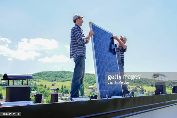 man installing solar panels - solarkraftwerk stock-fotos und bilder