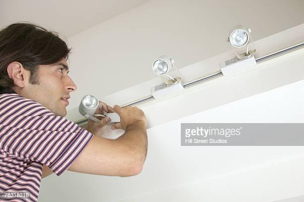 man installing track lighting in new home - accessorio per le lampade foto e immagini stock