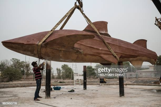 Man installs a metal sculpture of a whale shark at a public place in Djibouti, on July 6, 2018.