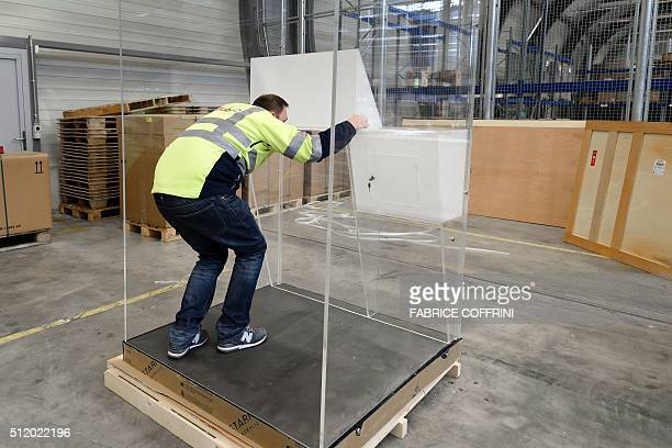 A man installs a transparent voting booth ordered by FIFA presidential contender Prince Ali bin alHussein at Zurich airport's freight area on...