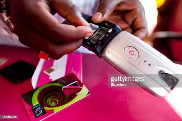A man installs a Zain SIM card in his cell phone in a store in Kampala Uganda on Thursday Feb 18 2010 Bharti Airtel Ltd India's biggest wireless...