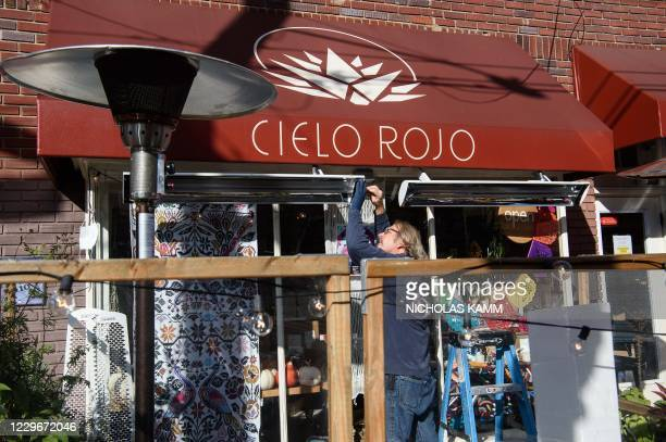 Man installs an outdoor heater outside a restaurant on November 18, 2020 in Takoma Park, Maryland, as the state imposes new restrictions to help...