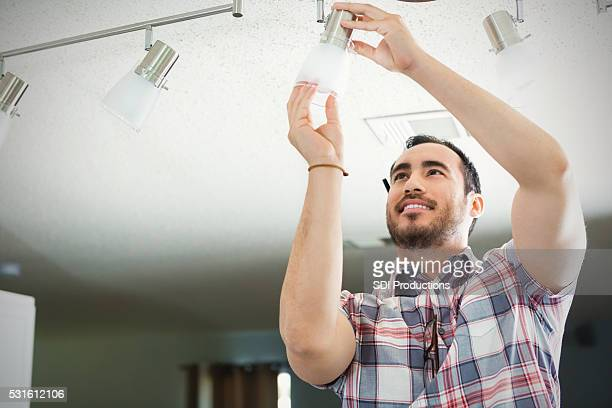 Man installs light fixture in new home