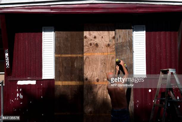 A man installs plywood over the windows of a mobile home at the Sunnyside Trailer Park during preparations for Hurricane Irma in West Miami Florida...