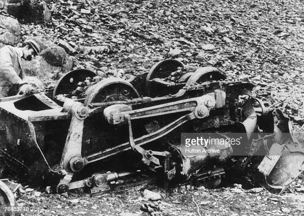 Man instpecting the remains of the Snowdonian Mountain Railway engine 'Ladas' which derailed and crashed at the bottom of a precipice on the opening...