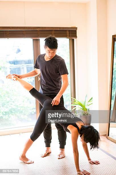 Man instructing woman practicing yoga in studio