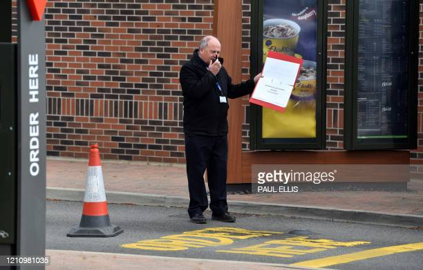 A man instructs a worker of Britain's NHS who has arrived by car to be tested for the novel coronavirus COVID19 at a testing centre set up at a...