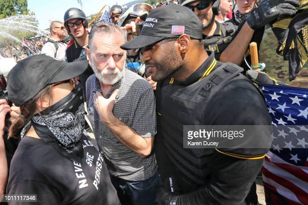 A man intervenes during an argument between protesters during a rally for gun rights' laws and free speech at Tom McCall Waterfront Park on August 4...