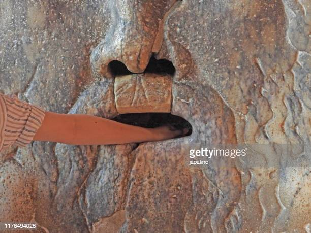 a man introducing his hand in the bocca della veritta - ancient civilization stock pictures, royalty-free photos & images