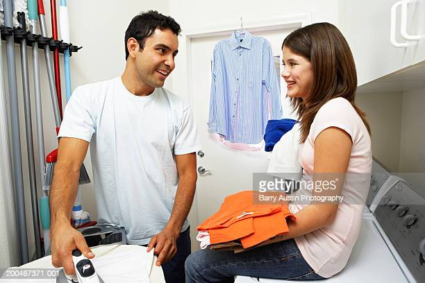 Man ironing in laundry room, girl (9-11) sitting on washing machine