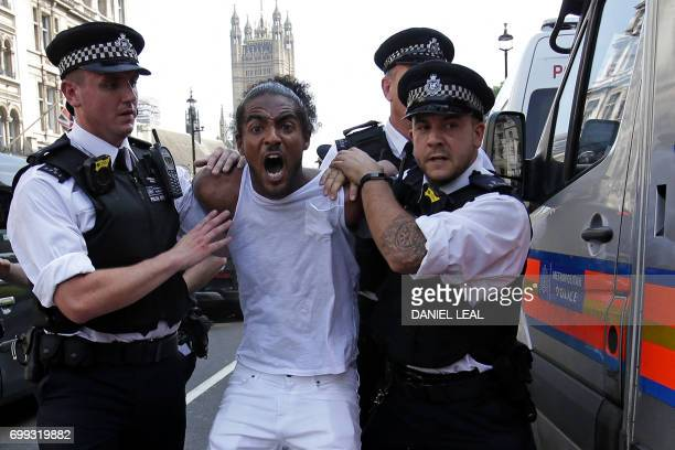 A man is apprehended by police officers as protesters gather in Parliament Square after marching through central London on June 21 during an...