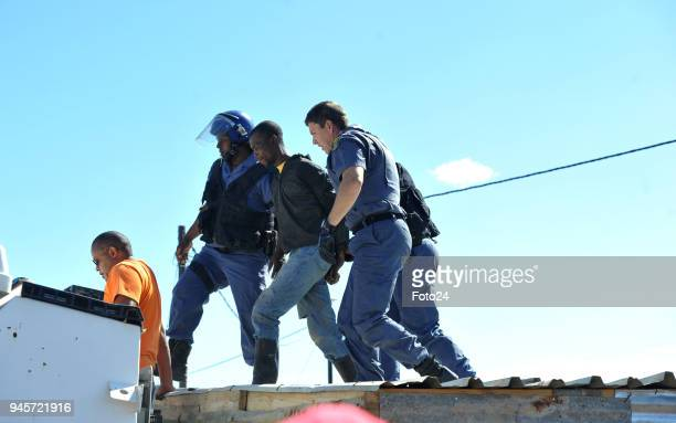 A man is apprehended by police on the roof of of a shack after flinging his sixmonthold baby at the Joe Slovo informal settlement on April 12 2018 in...
