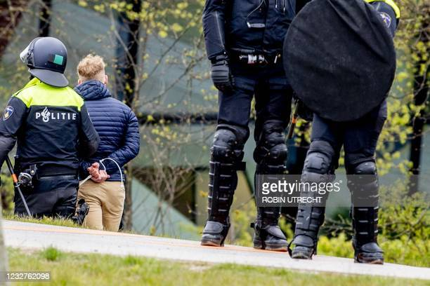 Man is arrested by police officers after Feyenoord fans threw fireworks and stones at the police in Rotterdam, on May 8 following a supporters'...