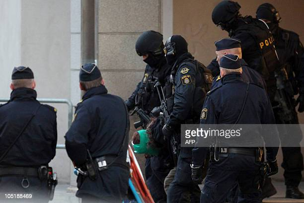 A man is arrested by police officers at the entrance of a building in Storgatan in central Malmo on October 11 2010 after he grabbed a twoyearold boy...