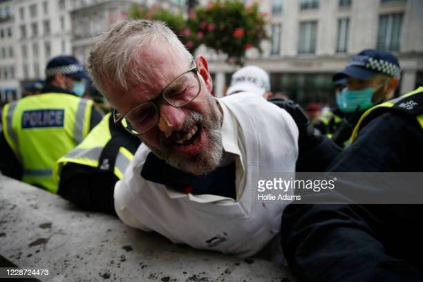 A man is arrested by police officers during a We Do Not Consent antilockdown rally at Trafalgar Square on September 26 2020 in London England...