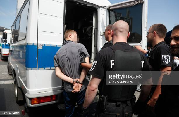 A man is arrested by police officers in Berlin's Schoeneberg district where a suspicious car was found shortly before an event to celebrate the 100th...